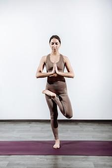 Junge frauentrainerin, die trainer yoga in der halle stehend übt vrikshasana baumhaltung aus