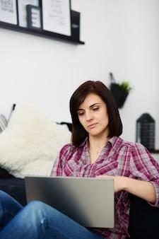 Junge freiberuflerfrau, die laptop verwendet.