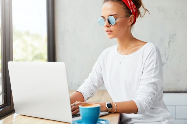 Junge freiberuflerin arbeitet remote am laptop im café, gibt tastaturinformationen aus und trinkt kaffee. frau chattet mit freunden in sozialen netzwerken, verbunden mit drahtlosem internet im restaurant