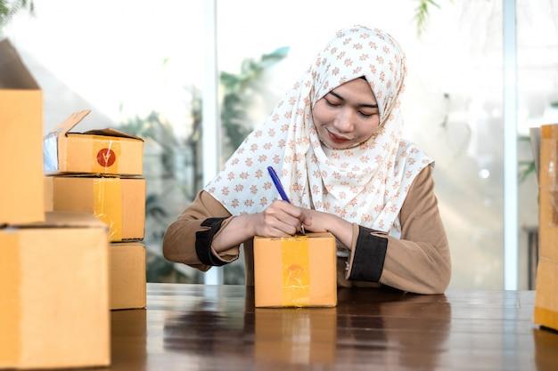 Junge freiberuflerin, die hijab-schrift auf einer schachtel trägt
