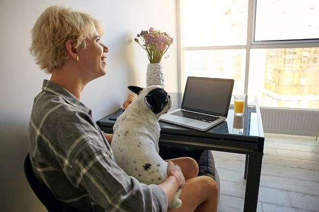 Junge freiberufliche frau, die entfernt von zu hause arbeitet, indem sie einen tragbaren computer benutzt, am tisch neben dem fenster sitzt und ihren hund hält, in guter stimmung ist