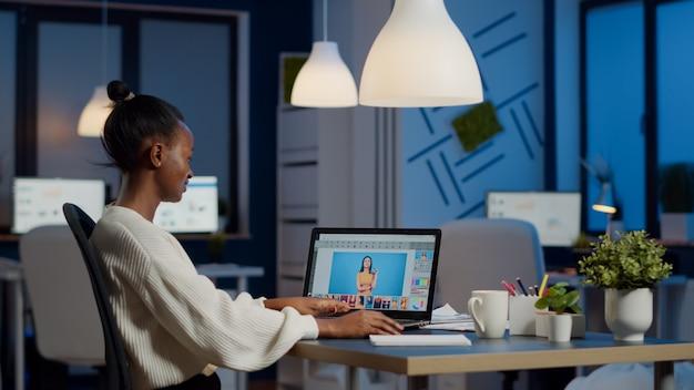 Junge freiberufliche retuscheurin, die überstunden am laptop mit bildbearbeitungssoftware macht