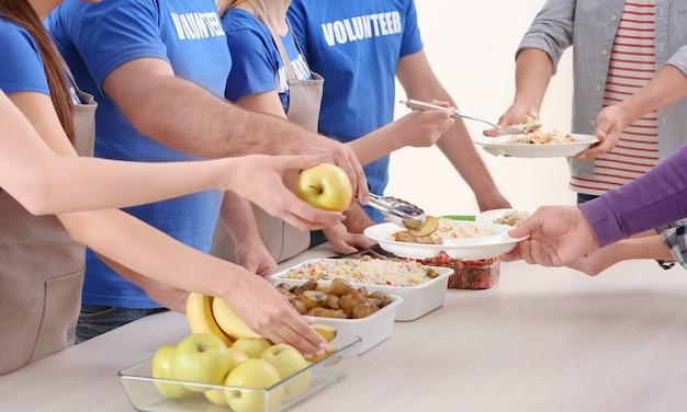 Junge freiwillige, die obdachlosen essen servieren
