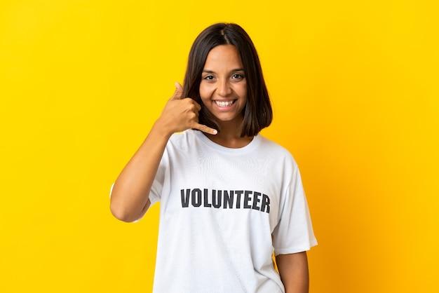 Junge freiwillige frau lokalisiert auf gelbe, die telefongeste macht. rufen sie mich zurück zeichen
