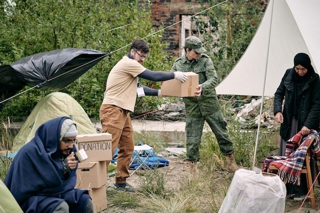 Junge freiwillige und vertreterin des migrationsdienstes, die spende verbreiten