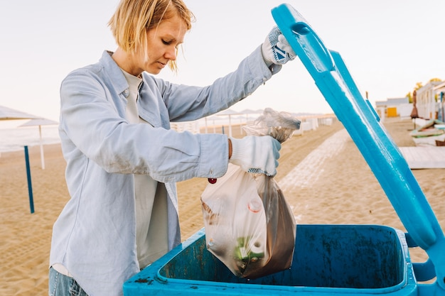 Junge freiwillige wirft müllsack in mülleimer am strand.