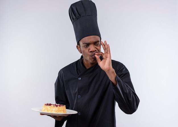 Junge freudige afroamerikanische köchin in der kochuniform hält kuchen auf teller und gestikuliert lecker köstlich lokalisiert auf weißer wand