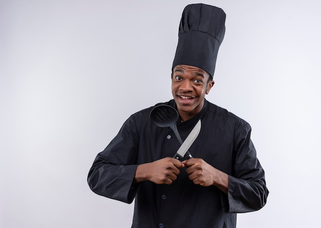 Junge freudige afroamerikanische köchin in der kochuniform hält messer und spatel lokalisiert auf weißer wand