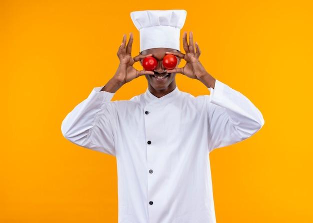 Junge freudige afroamerikanische köchin in der kochuniform schließt augen, die tomaten mit den händen lokalisiert auf orange wand halten