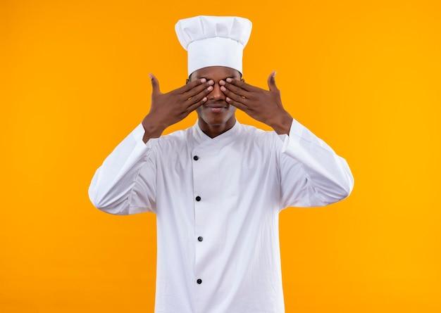 Junge freudige afroamerikanische köchin in der kochuniform schließt augen mit den händen, die auf orange wand lokalisiert werden
