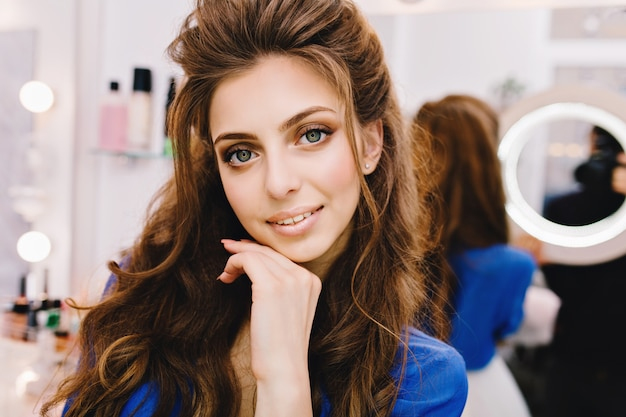 Junge freudige frau des nahaufnahmeporträts im blauen hemd mit dem langen brünetten haar, das positive emotionen zur kamera im schönheitssalon ausdrückt