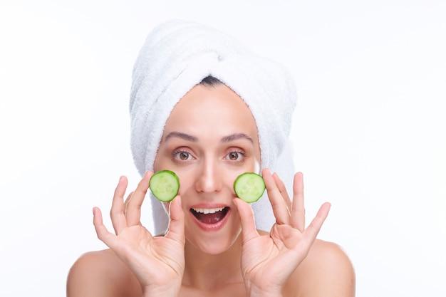 Junge freudige frau mit gesunder strahlender haut, die zwei scheiben frische saftige gurke durch ihre wangen nach dem baden oder duschen hält