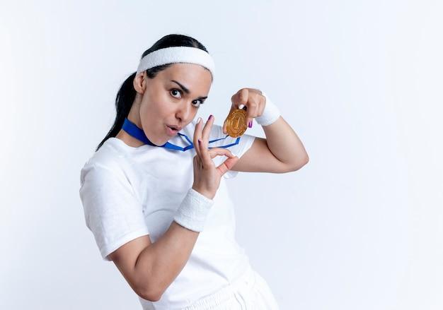 Junge freudige kaukasische sportliche frau, die stirnband und armbänder trägt, hält goldmedaille und gestikuliert ok handzeichen lokalisiert auf weißem raum mit kopienraum