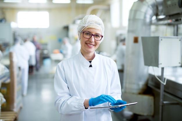 Junge freudige schöne arbeiterin in sterilen tüchern, die eine tablette halten und für die kamera nahe fabrikproduktionslinie lächeln.