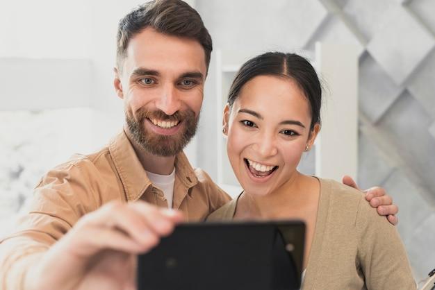Junge freunde des modells, die selfies im büro nehmen