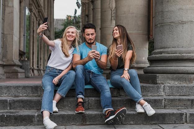 Junge freunde, die auf treppen sitzen und ein selfie nehmen