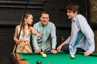 Junge Freunde, die Gespräch beim Spielen des Billards im Verein haben