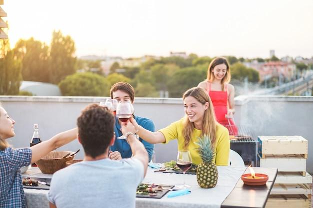 Junge freunde, die grillparty bei sonnenuntergang auf penthouse-terrasse haben