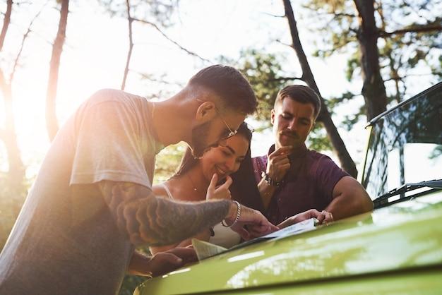 Junge freunde, die karte lesen, die auf der haube des modernen grünen jeeps im wald ist.