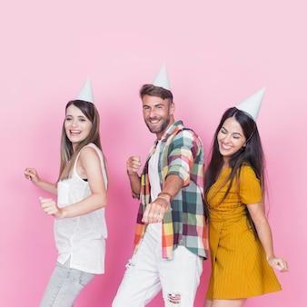 Junge freunde, die partyhuttanzen gegen rosa hintergrund tragen