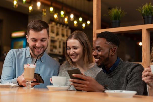 Junge freunde, die telefone am restaurant verwenden