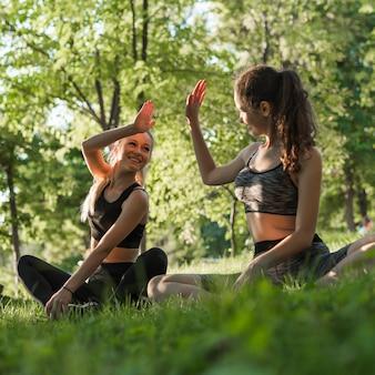 Junge freunde, die yoga im park tun