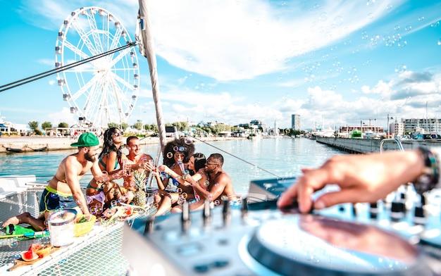 Junge freunde haben spaß beim toasten von wein auf einer segelbootparty