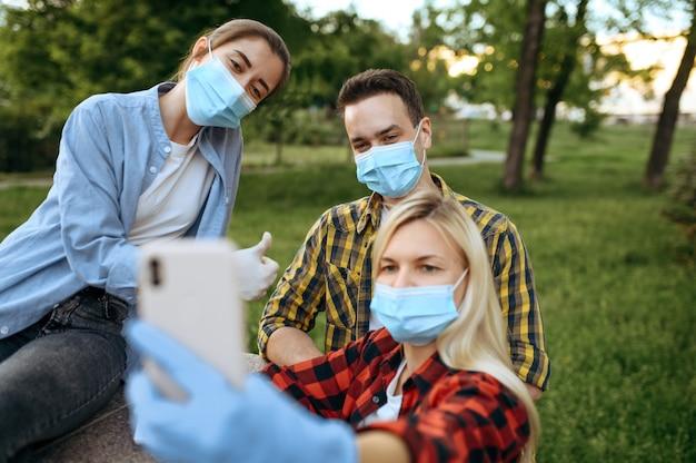 Junge freunde in masken und handschuhen machen selfie im park, quarantäne. weibliche person, die während der epidemie, der gesundheitsversorgung und des schutzes, des pandemischen lebensstils geht