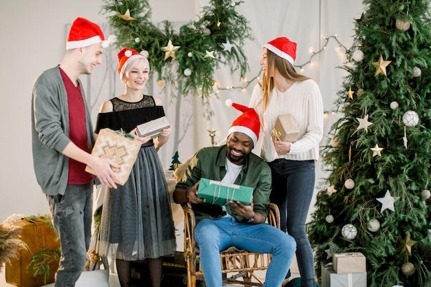 Junge freunde in weihnachtsmützen feiern weihnachten mit geschenkboxen