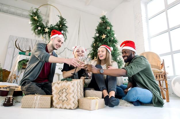 Junge freunde klirren gläser, die champagner auf weihnachtsfeier feiern