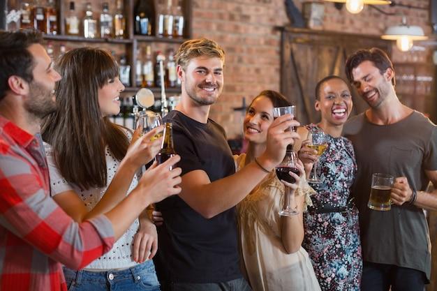 Junge freunde lachen zusammen, während sie getränke halten