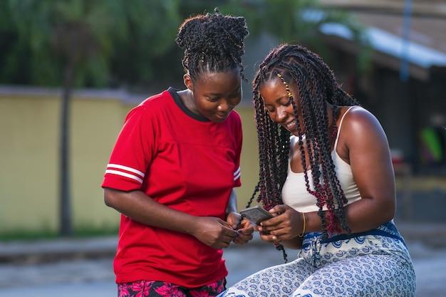 Junge freunde schauen auf das smartphone auf der straße