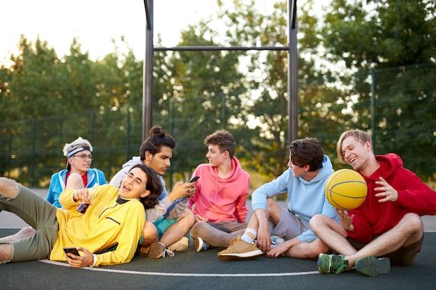 Junge freunde sitzen auf basketballplatz, entspannen sich und machen pause nach dem spiel