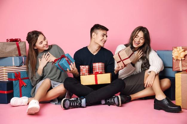 Junge freunde sitzen unter weihnachtsgeschenkboxen auf rosa