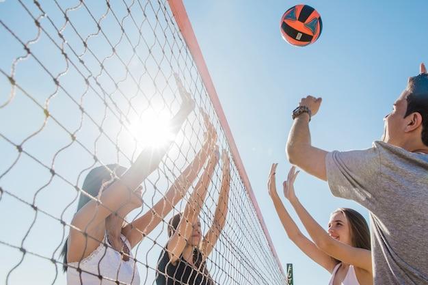 Junge freunde spielen volleyball