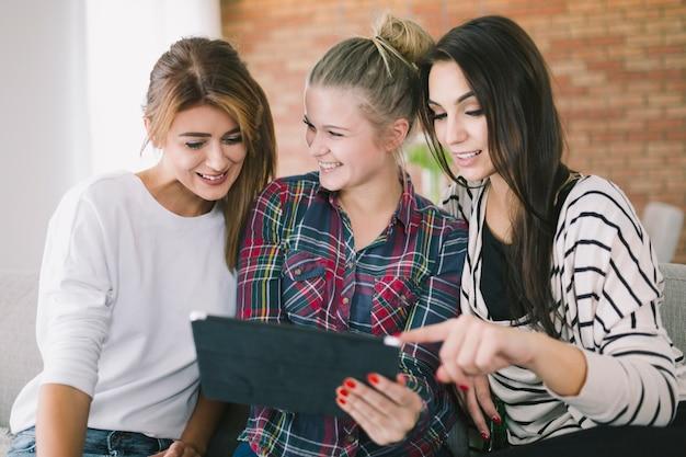 Junge freundinnen, die zusammen tablette aufpassen
