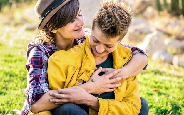 Junge freundinnen in der liebe, die zusammen zeit an der reisereise umarmt am park teilt