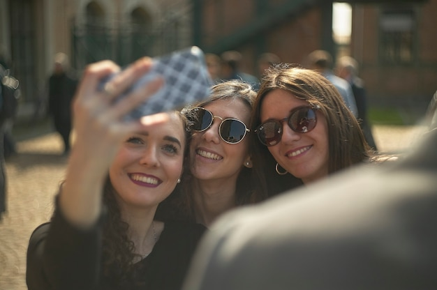 Junge freundinnen machen mit dem smartphone ein selfie im freien