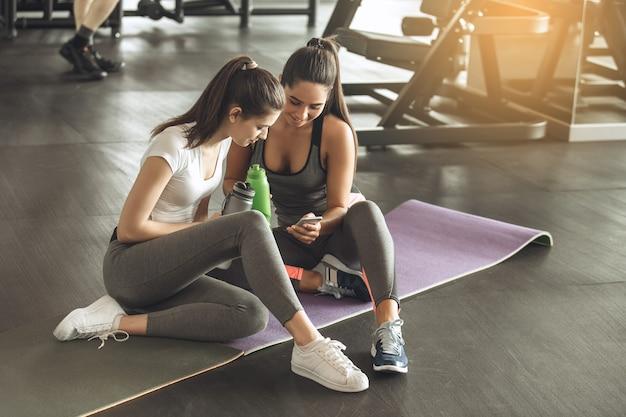 Junge freundinnen trainieren im fitnessstudio beim surfen auf dem smartphone