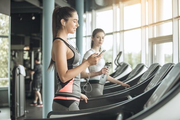 Junge freundinnen trainieren im fitnessstudio cardio