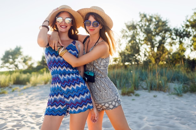 Junge freundinnen zusammen an einem strand bei sonnenuntergang