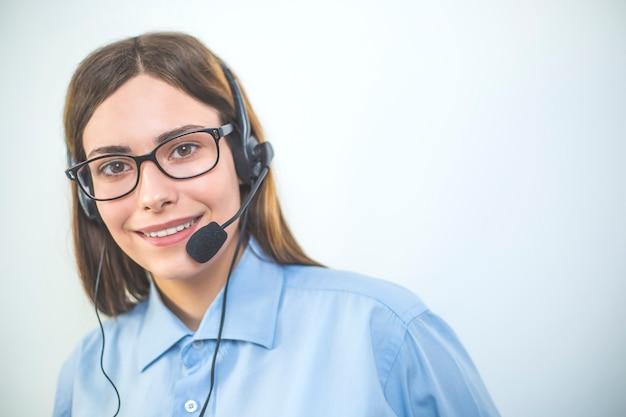 Junge freundliche agentin agentin mit headsets, die in einem callcenter arbeiten.