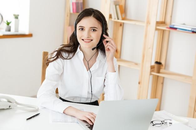 Junge freundliche betreiberin agentin oder geschäftsfrau mit headsets, die in einem callcenter arbeiten.