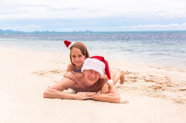 Junge freundliche familie vater und zwei dauthers freuen sich im sommer weihnachten am strand. weihnachten