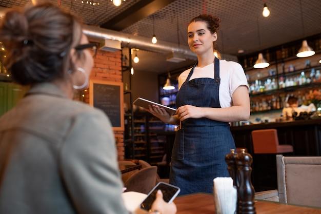 Junge freundliche kellnerin mit touchpad, die mit einem der kunden am tisch steht und ihre bestellung auf hintergrund der bartheke im restaurant entgegennimmt