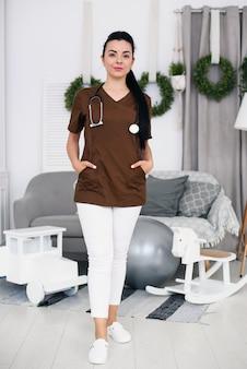 Junge freundliche kinderarztfrau mit stethoskop, die braune medizinische robe im modernen kindermedizinraum trägt. gesundheitswesen und medizinisches konzept.