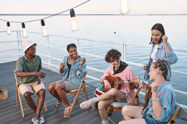 Junge freundliche leute singen mit gitarre, während sie am sommertag zeit auf dem pier verbringen?