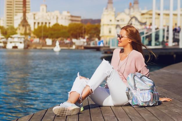 Junge frische hübsche frau, die auf hölzernem pier nahe meer sitzt und die stadt betrachtet. attraktives hipster-mädchen mit rucksack, das ihre ferien genießt. aktives lebensstilkonzept.