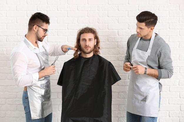 Junge friseure, die mit kunden gegen weißen backsteinhintergrund arbeiten