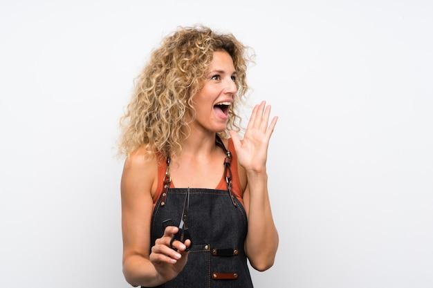 Junge friseurfrau über der lokalisierten wand, die mit dem breiten mund schreit, öffnen sich